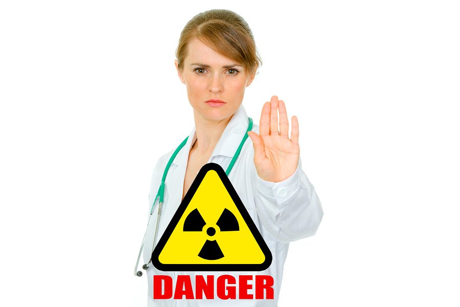 Concept- radiation danger! Strict medical female doctor showing stop gesture isolated on white