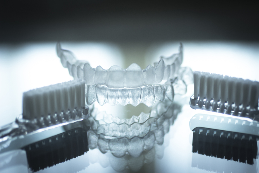 Invisible dental teeth brackets tooth aligners plastic braces retainers to straighten teeth and toothbrush dental hygien care. Orthodontic temporary removable straighteners in dental office dentists surgery clinic.Artistic color photo in creative blue ton