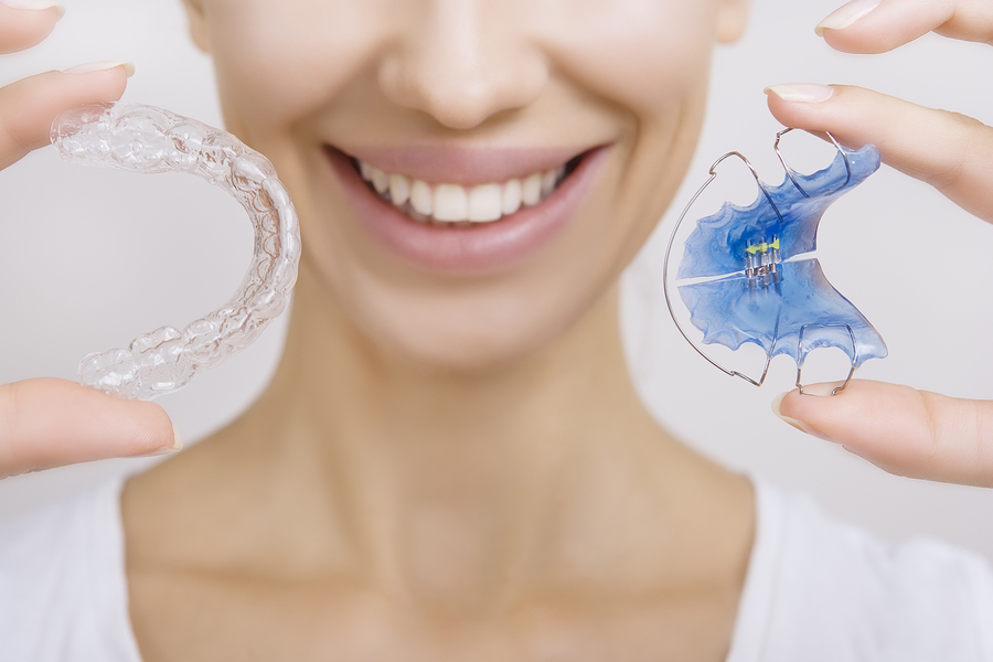 Beautiful Smiling girl Holding Retainer for Teeth (Dental Braces) and Individual Tooth Tray. Orthodontics Dental Theme Methods of Teeth (Bite) Correction Close-up