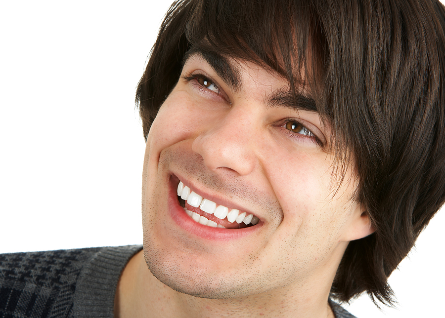 Face of a young smiling man. Over white background