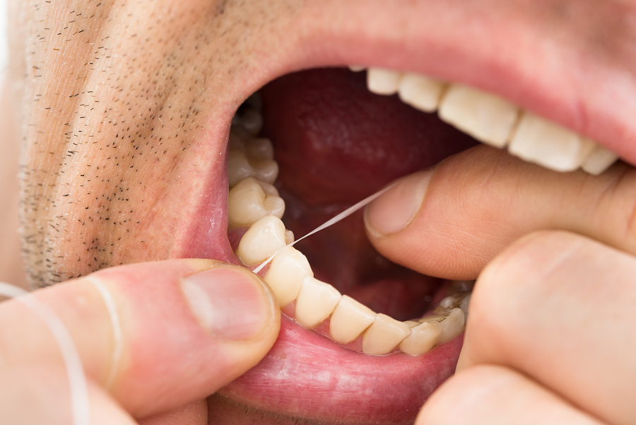 Close-up Photo Of A Man Flossing Teeth