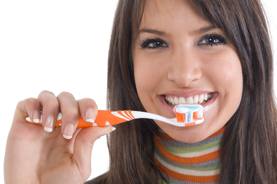 Young brunette girl with tooth brush in hand. Concept of health care and oral hygiene.