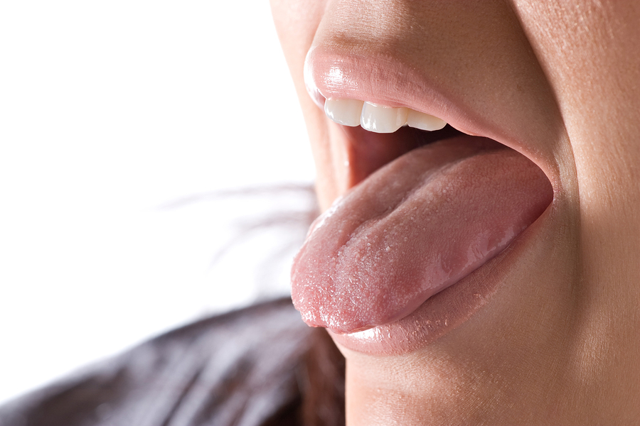 Closeup of a young woman sticking out her tongue.