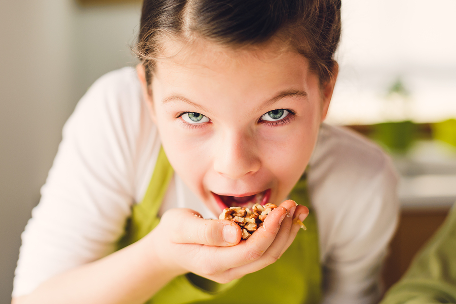 Healthy eating concept - young girl eating walnuts ** Note: Soft Focus at 100%, best at smaller sizes