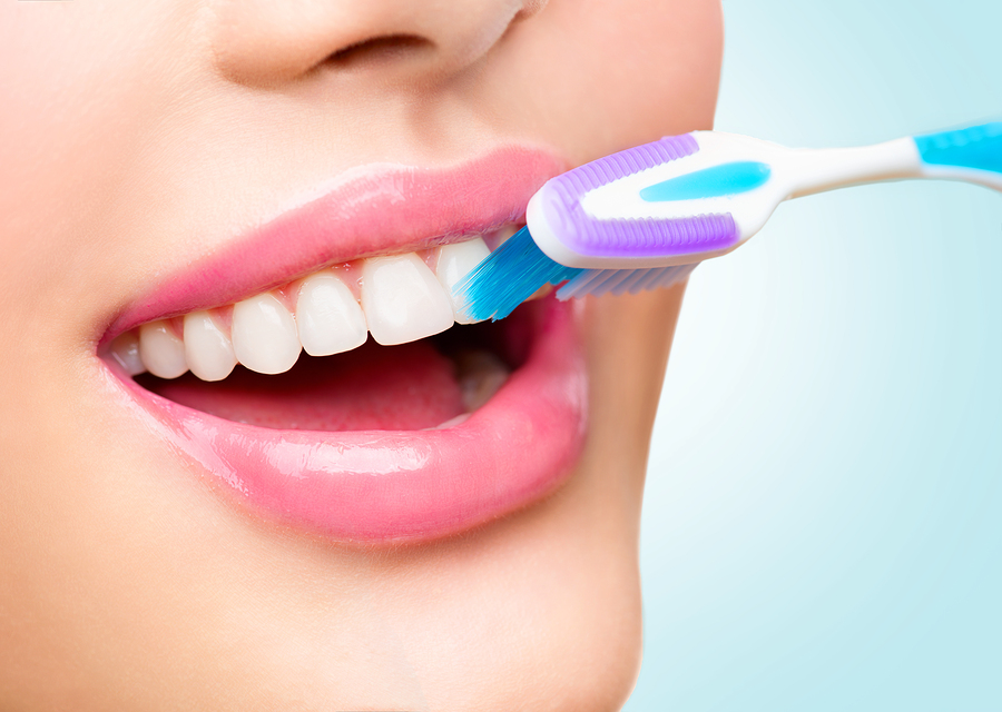Teeth brushing. Beautiful white healthy teeth. Closeup of happy woman brushing her teeth. Teeth whitening, dental care concept. Mouth of beauty girl with toothbrush